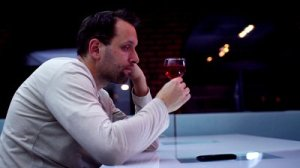 stock-footage-sad-lonely-man-drinking-wine-in-bar-and-looking-at-cellphone